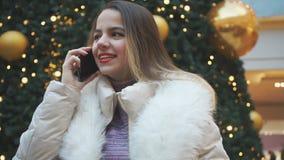 Junges schönes Mädchen, das auf dem Telefon und dem Lächeln spricht stock video