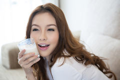 Junges schönes Mädchen, das ein Glas Milch hält stockbilder
