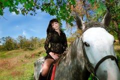 Junges schönes Mädchen, das ein Pferd auf Natur reitet Stockbild
