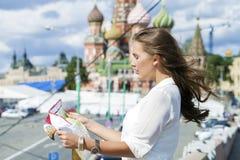 Junges schönes Mädchen, das eine touristische Karte von Moskau, Russland hält Lizenzfreie Stockfotos