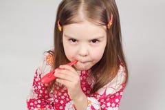 Junges schönes Mädchen, das einen roten Thermometer anhält Lizenzfreies Stockfoto