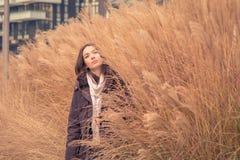 Junges schönes Mädchen, das in einer trockenen Rasenfläche aufwirft lizenzfreies stockbild