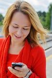 Junges schönes Mädchen, das Handy verwendet Stockbild