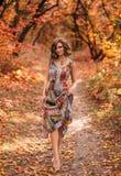 Junges schönes Mädchen, das in Herbstwald geht Stockfoto