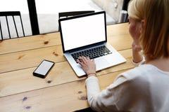 Junges schönes Mädchen, das in ihrem stilvollen Licht des Designers und in geräumigen Büro arbeiten an einem Laptop sitzt Stockfoto