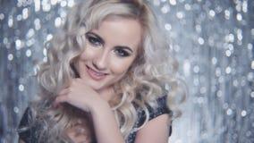 Junges schönes Mädchen, das im eleganten Kleid über glänzendem Hintergrund aufwirft stock video
