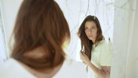 Junges schönes Mädchen, das im Spiegel im weißen Dekor schaut Langsame Bewegung stock video footage