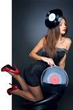 Junges schönes Mädchen, das im Studio mit Vinyldiskette aufwirft Stockfoto