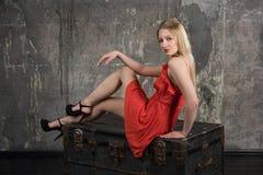 Junges schönes Mädchen, das im Studio im roten Kleid aufwirft stockbilder