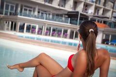 Junges schönes Mädchen, das im Swimmingpool stillsteht Stockbild