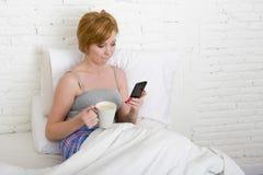 Junges schönes Mädchen, das Kaffee auf Bett bei der Anwendung des Internet-Handys im on-line-Sozialen Netz trinkt Lizenzfreie Stockfotos