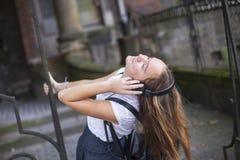 Junges schönes Mädchen, das Musik auf Kopfhörern auf der Straße genießt Lizenzfreie Stockbilder