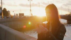 Junges schönes Mädchen, das selfie auf dem Hintergrund der Brücke in den hellen Strahlen der untergehenden Sonne nimmt 4K Stockfotos