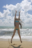 Junges schönes Mädchen, das am Strand springt Lizenzfreies Stockbild