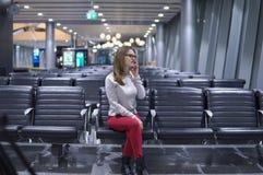 Junges, schönes Mädchen, das am Telefon in einem leeren Flughafenabfertigungsgebäude spricht Stockbilder