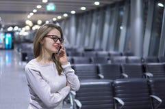 Junges, schönes Mädchen, das am Telefon in einem leeren Flughafenabfertigungsgebäude spricht Lizenzfreie Stockfotos