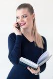 Junges schönes Mädchen, das am Telefon spricht, ein Tagebuch lächelt und hält Stockfoto