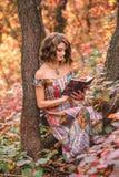 Junges schönes Mädchen, das unter einem Baum mit einem Buch sitzt Stockfotos