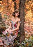 Junges schönes Mädchen, das unter einem Baum sitzt Stockfotografie
