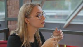 Junges schönes Mädchen in den Gläsern, die in einem Café, trinkender transparenter Tee von einem Glasbecher sitzen stock video footage