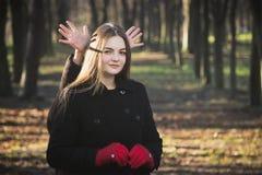 Junges schönes Mädchen in den roten Handschuhen eines schwarzen Mantels Frühling Forest Park erforschend stockfotografie