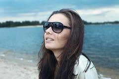 Junges schönes Mädchen in den Sonnegläsern auf einem Strand Stockbild