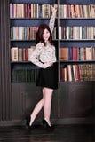 Junges schönes Mädchen in der Bibliothek Stockfotos