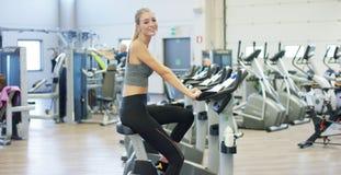 Junges schönes Mädchen in der Turnhalle, ihre Beine auf dem Radfahrensimulator rüttelnd und lächeln an der Kamera Das Konzept: zu Stockfoto
