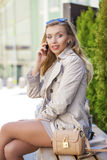 Junges schönes Mädchen in einem beige Mantel, telefonisch nennend und sitzen Stockfotografie