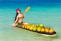 Junges schönes Mädchen in einem Bikini mit den tropischen Blumen, die i sitzen stockbild