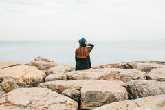 Junges schönes Mädchen in einem Hut sitzt auf den Felsen auf der Küste und untersucht den Abstand Rest, Ferien, Entspannung Stockbilder