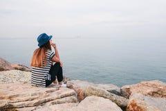 Junges schönes Mädchen in einem Hut sitzt auf den Felsen auf der Küste und untersucht den Abstand Rest, Ferien, Entspannung Lizenzfreie Stockfotografie