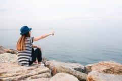 Junges schönes Mädchen in einem Hut sitzt auf den Felsen an der Küste und zeigt ihre Hand zum Abstand Rest, Ferien Lizenzfreies Stockbild