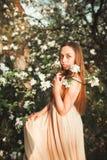 Junges schönes Mädchen in einem langen Kleid und in einem Kranz von Blumen nahe Fliederbusch des Gartens Lizenzfreie Stockfotos