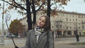 Junges schönes Mädchen in einem Mantel tut selfi Herbst in einer der Stadtstraßen stock video footage