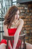 Junges schönes Mädchen in einem roten Kleid sitzt auf einem Holzstuhl in einem Café auf einer Straße in der Stadt von Lemberg Lizenzfreie Stockfotos