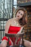 Junges schönes Mädchen in einem roten Kleid sitzt auf einem Holzstuhl in einem Café auf einer Straße in der Stadt von Lemberg Lizenzfreie Stockfotografie