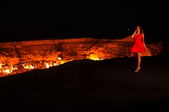 Junges schönes Mädchen in einem roten kurzen Kleid nahe dem brennenden Krater nachts Kunstretusche lizenzfreies stockfoto