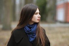 Junges schönes Mädchen in einem schwarzen Mantel und blauer Schal für einen Weg im Herbst/im Frühling parken Ein elegantes Brunet lizenzfreie stockfotos
