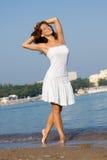 Junges schönes Mädchen in einem weißen Kleid auf dem Strand Lizenzfreie Stockfotografie