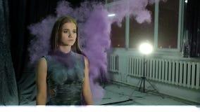 Junges schönes Mädchen in einer holi Farbenwolke auf einem dunklen Hintergrund, Zeitlupe stock footage