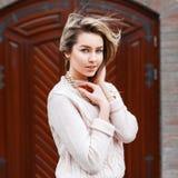 Junges schönes Mädchen in einer Strickjacke auf dem Hintergrund der Tür Lizenzfreies Stockfoto