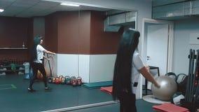 Junges schönes Mädchen in einer Turnhalle, die SitzenUPS mit einem Angriff vorwärts tut stock footage