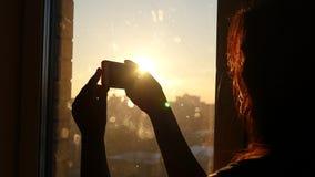Junges schönes Mädchen fährt einen Finger am Telefon nahe einem Fenster bei Sonnenuntergang, Zeitlupe, HD stock video footage