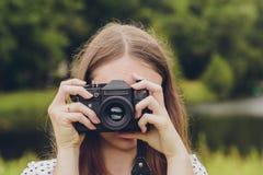 Junges schönes Mädchen fotografierte in der alten Weinlesekamera stockbild