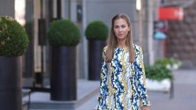 Junges schönes Mädchen geht hinunter die Stadtstraße mit Einkaufstaschen nach einem erfolgreichen Einkaufen Brunette in einem Kle stock video