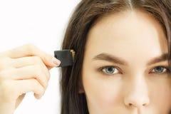 Junges schönes Mädchen hält einen USB-Blitz-Antrieb zu seinem Tempel Lizenzfreies Stockfoto