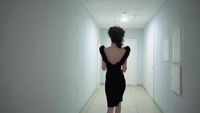 Junges schönes Mädchen im Büro, im Glättungskleid, gehend entlang den Korridor Langsame Bewegung stock video footage