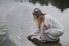 Junges schönes Mädchen im belarussischen Trachtenkleid mit einem Kranz Stockbild
