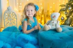 Junges schönes Mädchen im blauen weißen eleganten Abendkleid, das auf Boden nahe Weihnachtsbaum und Geschenken auf einem neuen Ja stockfotos